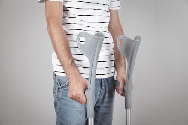 Hombre caucásico con muletas en pared gris