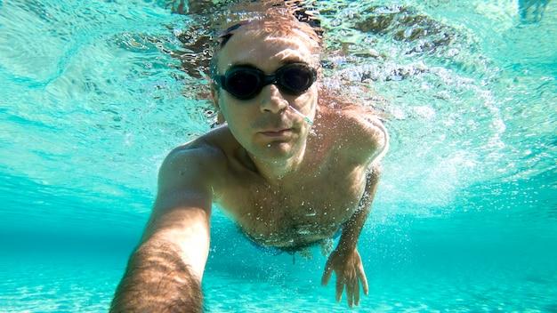 Hombre caucásico nadando bajo el agua en gafas de natación agua azul transparente