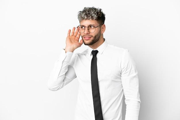 Hombre caucásico de negocios aislado sobre fondo blanco escuchando algo poniendo la mano en la oreja