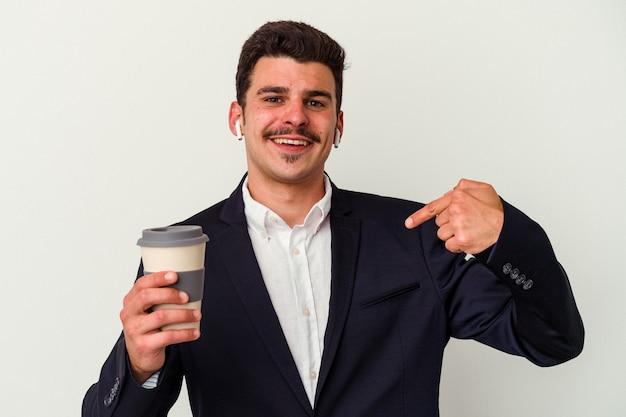 Hombre caucásico de negocios joven con auriculares inalámbricos y sosteniendo tomar café aislado sobre fondo blanco persona apuntando con la mano a un espacio de copia de camisa, orgulloso y confiado