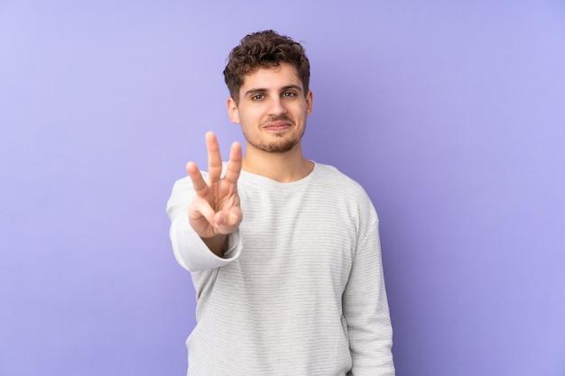 Hombre caucásico en pared púrpura feliz y contando tres con los dedos