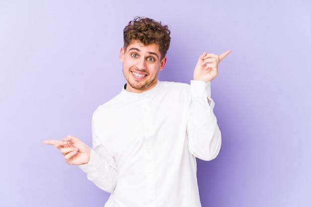 Hombre caucásico de pelo rizado rubio joven aislado apuntando a diferentes espacios de copia, eligiendo uno de ellos, mostrando con el dedo.