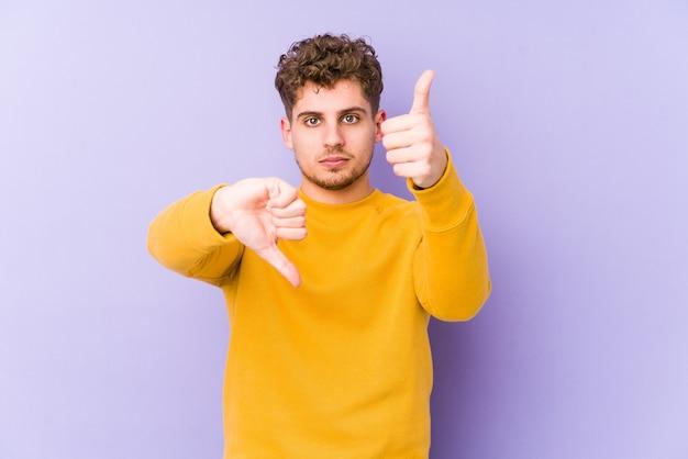 Hombre caucásico de pelo rizado rubio joven aislado mostrando los pulgares hacia arriba y hacia abajo, concepto de elección difícil