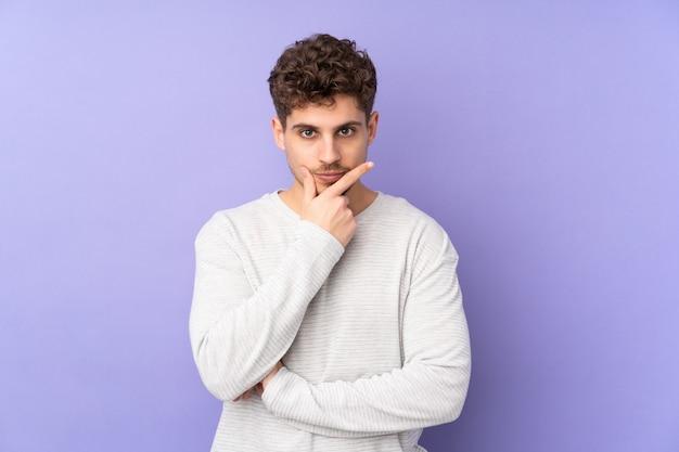 Hombre caucásico en pensamiento de pared púrpura
