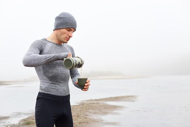 Hombre caucásico de pie en la orilla del río en un día brumoso y bebiendo té