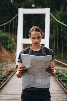 Hombre caucásico que mira un viaje del mapa y explora el concepto