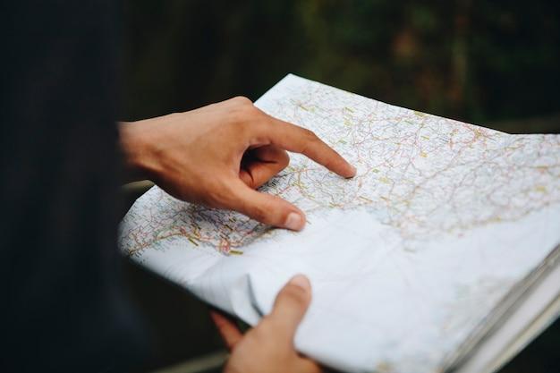 El hombre caucásico que mira un viaje del mapa y explora concepto