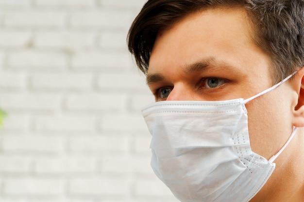 Hombre caucásico que se queda en casa durante la cuarentena de coronavirus / covid-19 con máscara médica