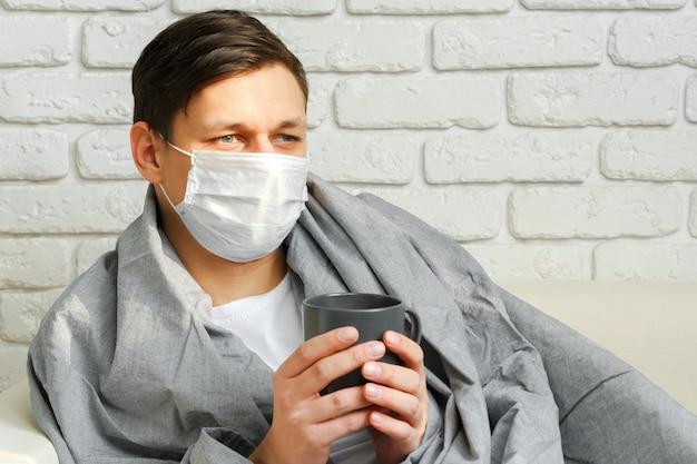 Hombre caucásico quedarse en casa durante la cuarentena covid-19 con máscara médica