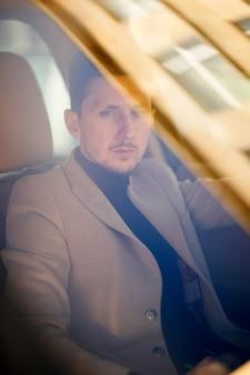 El hombre caucásico rico y moderno está sentado en un auto nuevo y moderno y mira seriamente a través del parabrisas
