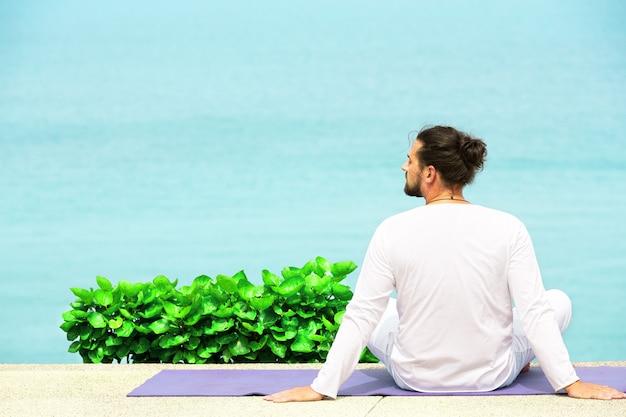 Hombre caucásico en ropa blanca meditando yoga en el muelle de la orilla del mar