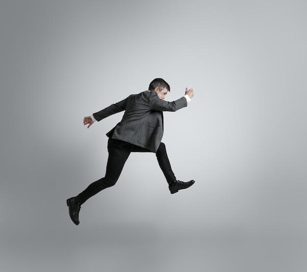 Hombre caucásico en ropa de oficina corriendo aislado en pared gris