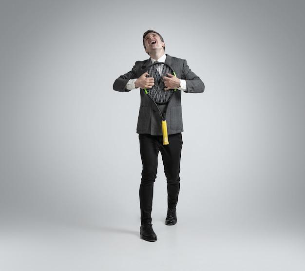 Hombre caucásico en ropa de oficina juega tenis aislado en pared gris
