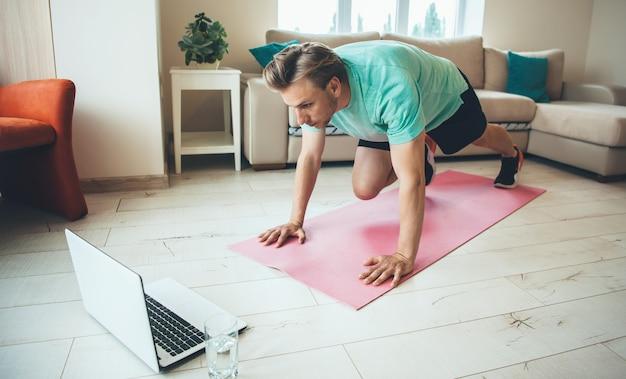 Hombre caucásico rubio concentrado haciendo ejercicios de estiramiento en la alfombra de yoga mientras mira la computadora portátil con un vaso de agua cerca