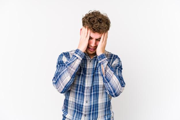 El hombre caucásico rubio joven del pelo rizado aisló quejarse y llorar desconsoladamente.