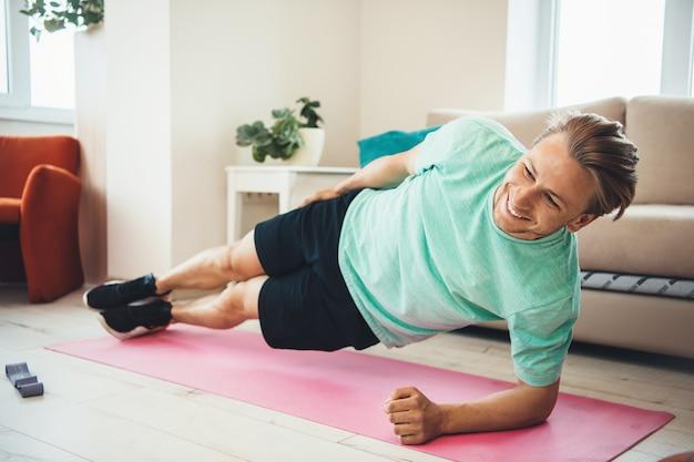 Hombre caucásico rubio sonriendo mientras hace ejercicios en una alfombra de yoga en casa