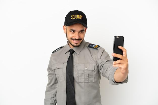 Hombre caucásico de seguridad joven aislado sobre fondo blanco haciendo un selfie