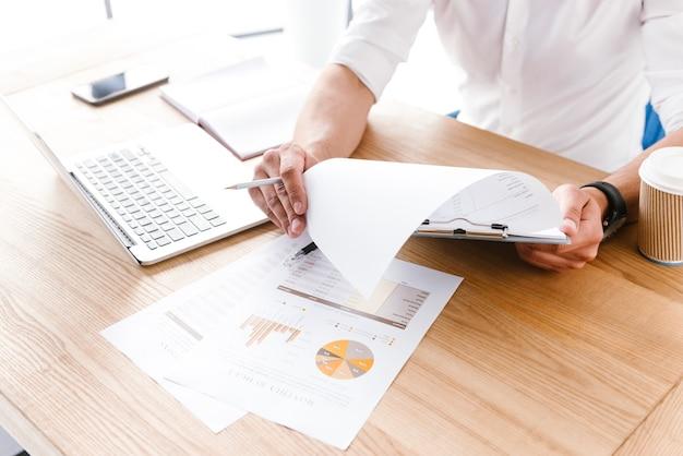 Hombre caucásico sentado a la mesa en la oficina y examinar datos o estadísticas, mientras sostiene el portapapeles con papel