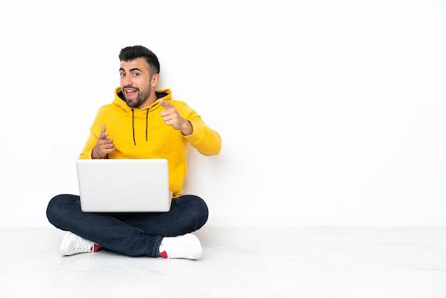Hombre caucásico sentado en el suelo con su computadora portátil apuntando hacia el frente y sonriendo