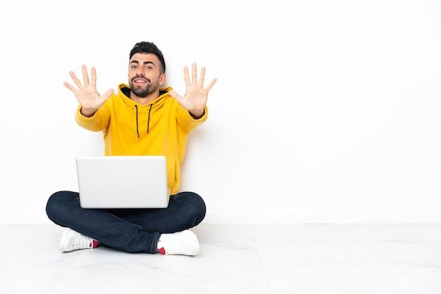 Hombre caucásico sentado en el suelo con su computadora portátil contando diez con los dedos