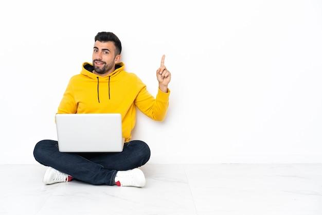 Hombre caucásico sentado en el suelo con su computadora portátil mostrando y levantando un dedo en señal de lo mejor