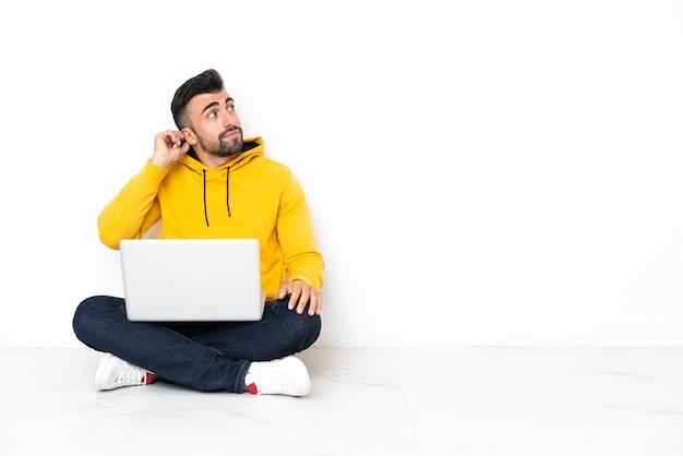 Hombre caucásico sentado en el suelo con su computadora portátil pensando en una idea