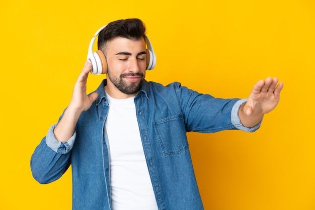 Hombre caucásico sobre pared amarilla aislada escuchando música y bailando