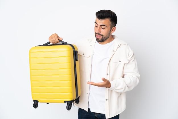 Hombre caucásico sobre pared blanca aislada en vacaciones con maleta de viaje