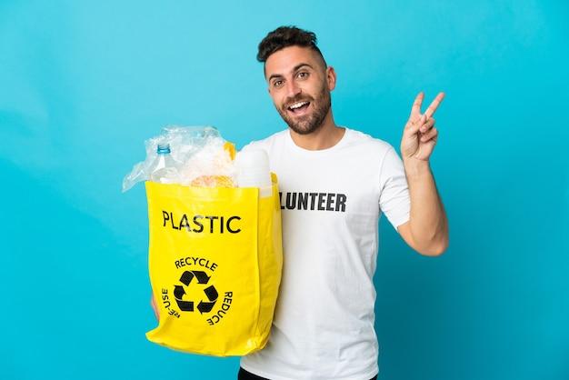 Hombre caucásico sosteniendo una bolsa llena de botellas de plástico para reciclar aislado sobre fondo azul sonriendo y mostrando el signo de la victoria