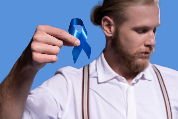 Hombre caucásico sosteniendo una cinta azul