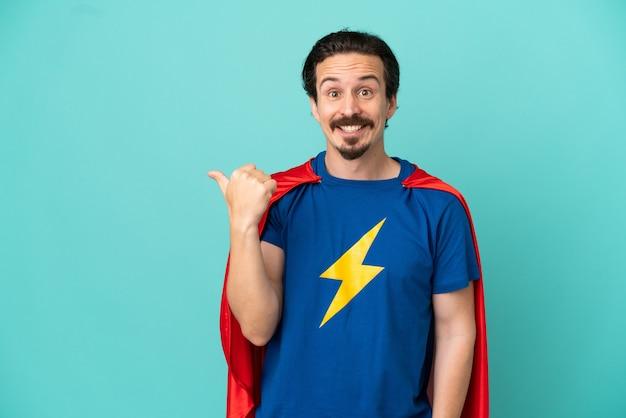 Hombre caucásico de superhéroe aislado sobre fondo azul apuntando hacia el lado para presentar un producto
