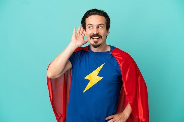 Hombre caucásico de superhéroe aislado sobre fondo azul escuchando algo poniendo la mano en la oreja