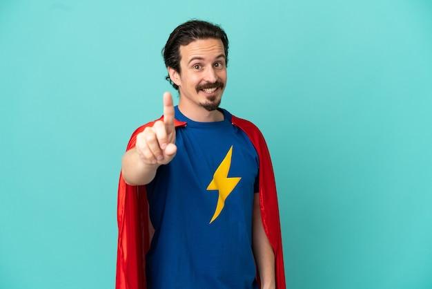 Hombre caucásico de superhéroe aislado sobre fondo azul mostrando y levantando un dedo