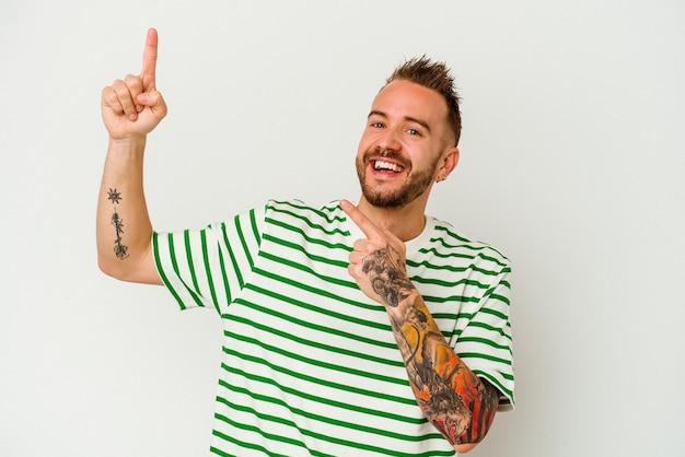 Hombre caucásico tatuado joven aislado sobre fondo blanco bailando y divirtiéndose.