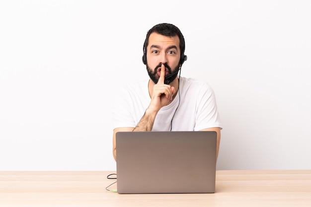 Hombre caucásico de telemarketer que trabaja con un auricular y con un ordenador portátil que muestra una señal de gesto de silencio poniendo el dedo en la boca.
