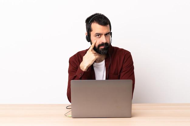 Hombre caucásico de telemarketing que trabaja con un auricular y con una computadora portátil que muestra algo.