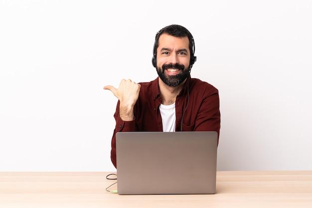 Hombre caucásico de telemarketing que trabaja con un auricular y con un portátil apuntando hacia el lado para presentar un producto.