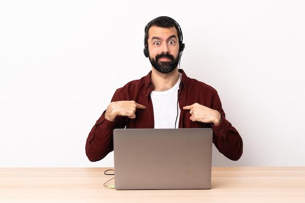 Hombre caucásico de telemarketing que trabaja con un auricular y con un portátil apuntando a sí mismo.