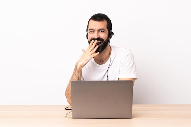 Hombre caucásico de telemarketing que trabaja con un auricular y con un portátil feliz y sonriente cubriendo la boca con la mano.