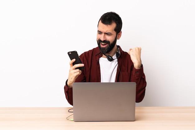 Hombre caucásico de telemarketing que trabaja con un auricular y con un portátil