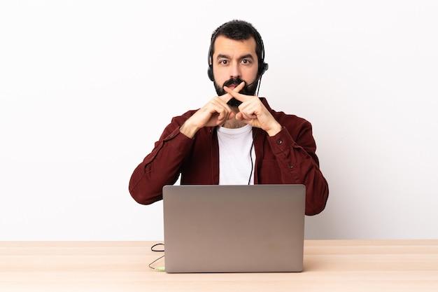 Hombre caucásico de telemercadeo que trabaja con un auricular y con un portátil mostrando un signo de gesto de silencio.