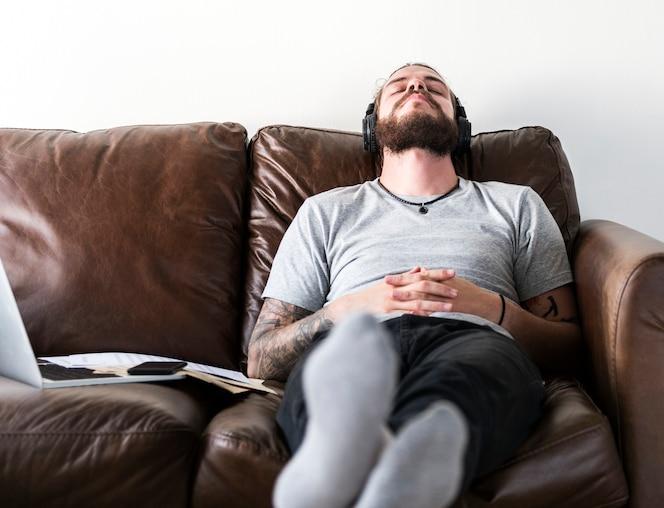 Hombre caucásico tomando un descanso del trabajo escuchando música