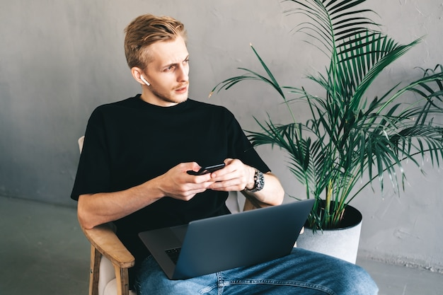 Hombre caucásico, trabajador autónomo, sentado en un sillón, con teléfono inteligente y computadora portátil.