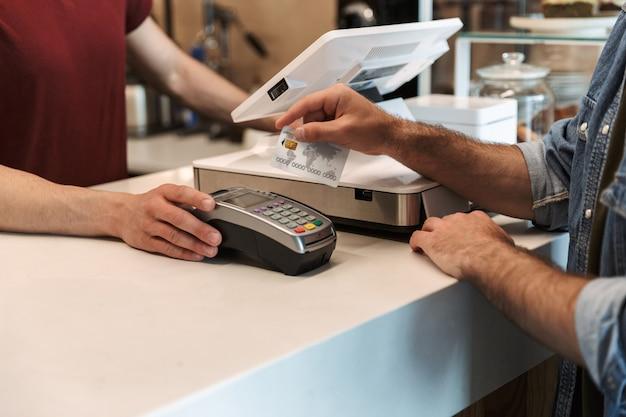 Hombre caucásico vestido con camisa de mezclilla pagando con tarjeta de débito en el café mientras el camarero sujeta la terminal de pago