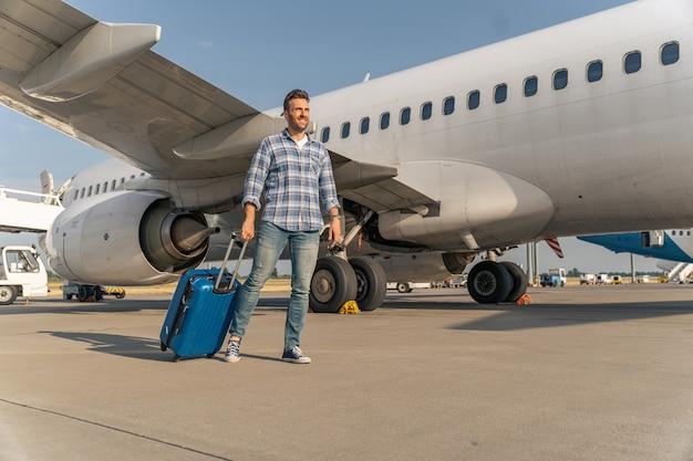 Hombre caucásico viajero bajarse del avión con maleta en el aeropuerto