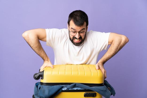 Hombre caucásico viajero con una maleta llena de ropa sobre púrpura aislado