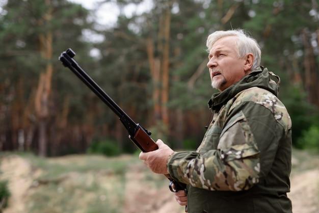 Hombre cazador atento con escopeta mirando hacia arriba.