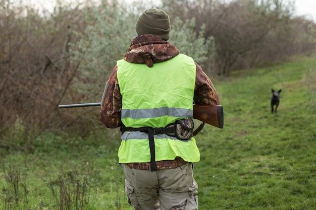Hombre cazador en camuflaje con una pistola durante la caza en busca de aves silvestres o caza