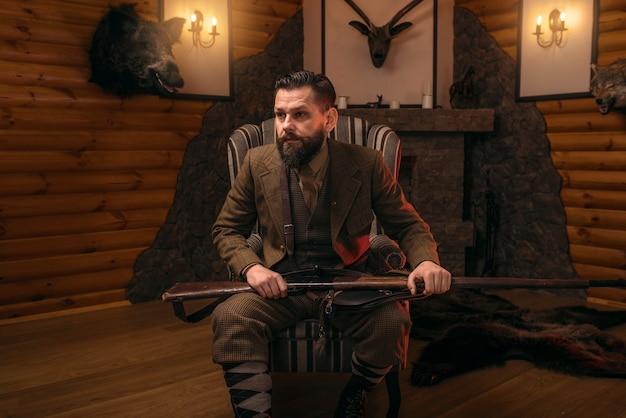 Hombre cazador con pistola vieja contra el cofre antiguo