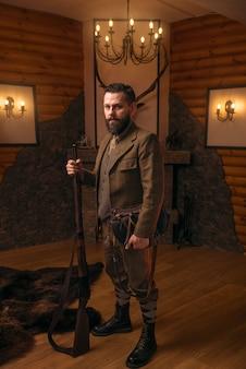 Hombre cazador sólido con ropa de caza antigua con pistola antigua contra chimenea.